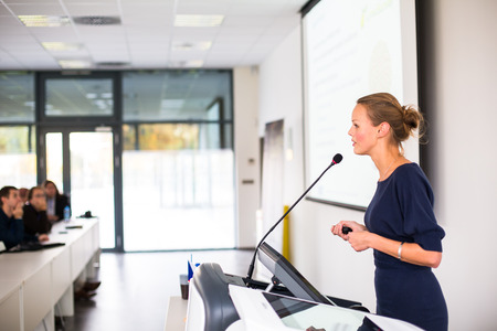 Foto de Pretty, young business woman giving a presentation in a conference/meeting setting (shallow DOF; color toned image) - Imagen libre de derechos