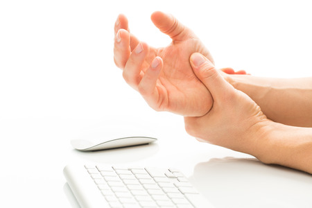 Working too much - suffering from a Carpal tunnel syndrome - young man holding his wrist in pain due to prolonged use of keyboard and mouse over white background