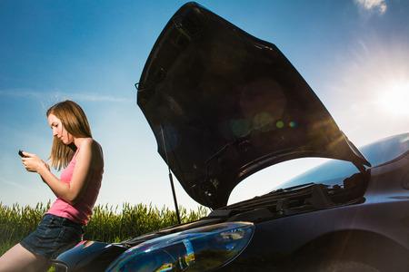 Foto de Pretty, young woman calling the roadside service/assistance after her car has broken down - Imagen libre de derechos