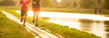 Foto de Couple running outdoors, at sunset, by a river, staying active and fit - Imagen libre de derechos