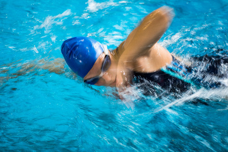 Photo pour Female swimmer in an indoor swimming pool - doing crawl (shallow DOF) - image libre de droit
