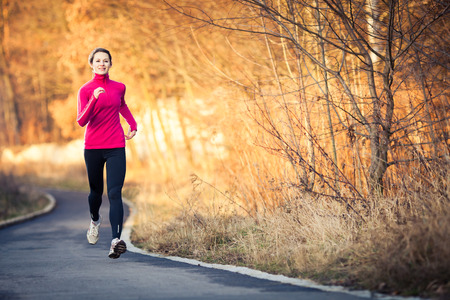 Photo pour Young woman running outdoors in a city park on a cold fall/winter day - image libre de droit