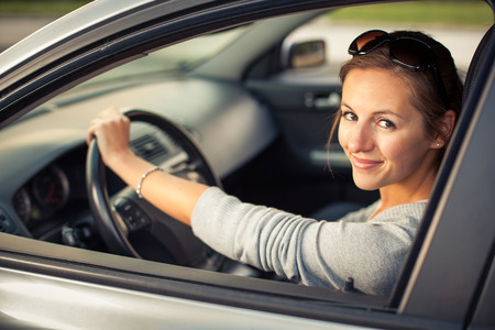 Photo for Pretty young woman driving her new car  (color toned image; shallow DOF) - Royalty Free Image