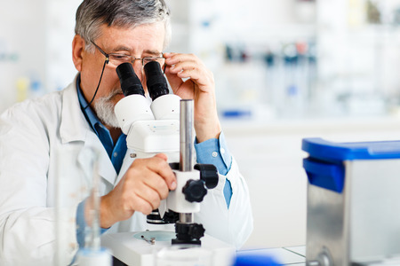 Foto de senior male researcher carrying out scientific research in a lab using a microscope (shallow DOF; color toned image) - Imagen libre de derechos