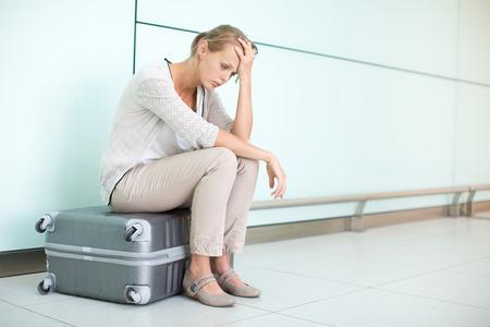 Foto de Young, female frustrated passenger at the airport, waiting desperately for her delayed flight (color toned image; shallow DOF) - Imagen libre de derechos