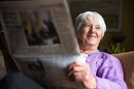 Photo pour Senior woman reading morning newspaper, sitting in her favorite chair in her living room, looking happy - image libre de droit