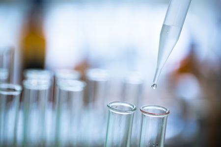 Foto de Liquid drop from laboratory glass pipette to test tube - Imagen libre de derechos