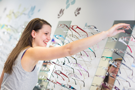 Foto de Pretty, young woman choosing new glasses frames in an optician store (color toned image; shallow DOF) - Imagen libre de derechos