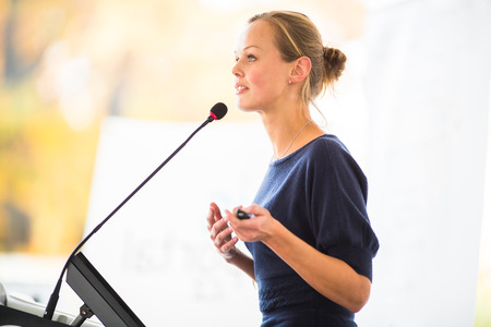 Photo pour Pretty, young business woman giving a presentation in a conference/meeting setting  - image libre de droit