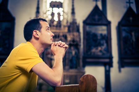 Photo pour Handsome young man praying in a church - image libre de droit