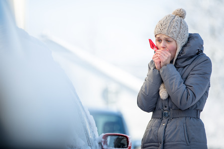 Foto de Young woman cleaning her car from snow and frost on a winter morning, she is freezing and needs to get to work - Imagen libre de derechos