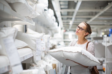 Photo pour Pretty, young woman choosing the right pillow for her bed in a modern home furnishings store (color toned image; shallow DOF) - image libre de droit