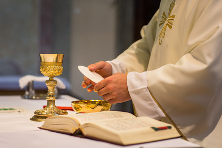 Photo for Priest during a wedding ceremony/nuptial mass (shallow DOF; color toned image) - Royalty Free Image