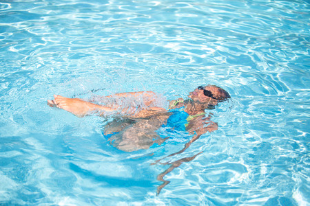 Photo pour Young woman in a swimming pool performing some synchronized swimming drills - image libre de droit