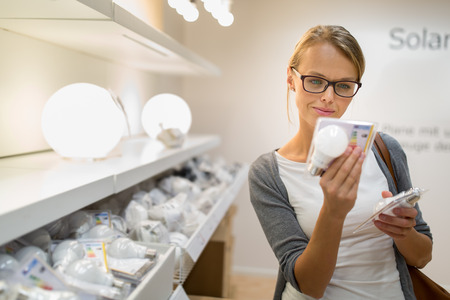Foto de Energy efficient lighting choice: Pretty, young woman holding and choosing a LED diode light bulb for her lamp in DIY department store - Imagen libre de derechos