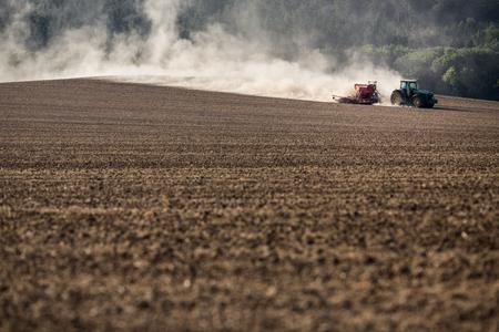 Photo pour Tractor plowing a dry farm field - image libre de droit