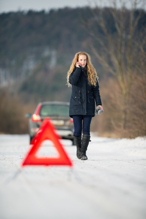 Foto de Young woman setting up a warning triangle and calling for assistance after her car broke down in the middle of nowhere on a freezing winter day - Imagen libre de derechos