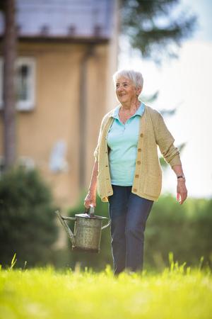Foto de Senior woman doing some gardening in her lovely garden - Imagen libre de derechos
