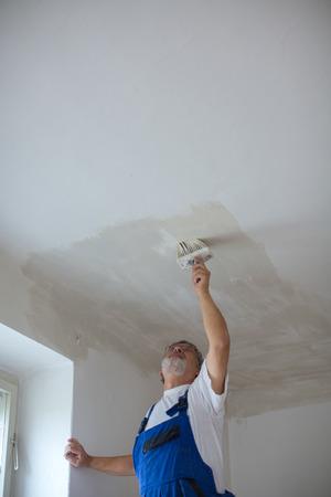 Foto de Senior painter man at work with a paint bucket - Imagen libre de derechos