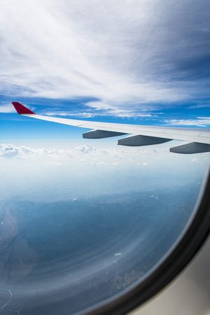 Photo pour An airplane wing through airplane window with blue sky background - image libre de droit