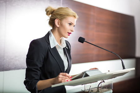 Photo for Pretty, young business woman giving a presentation in a conference/meeting setting (shallow DOF; color toned image) - Royalty Free Image