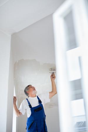 Foto de Senior painter man at work with a paint bucket, wall painting concept - Imagen libre de derechos