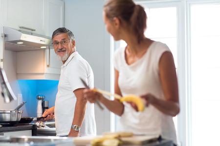 Foto de Senior man cooking in a bright modern kitchen together with his daughter, having a blast (color toned image) - Imagen libre de derechos