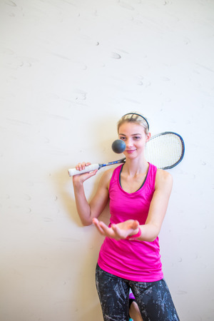 Photo pour Cute young woman with a racket leaning against a wall in a squash court, ready for the game - image libre de droit