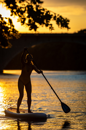Photo for SUP Stand up paddle board concept - Pretty, young woman paddle boarding on a lovely lake in warm late afternoon light - shot from underwater - Royalty Free Image