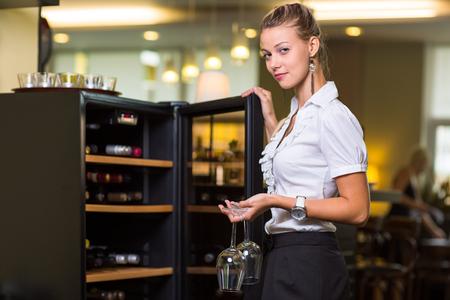 Foto de Cute waitress getting a bottle of a nice wine for the guests in a restaurant - Imagen libre de derechos