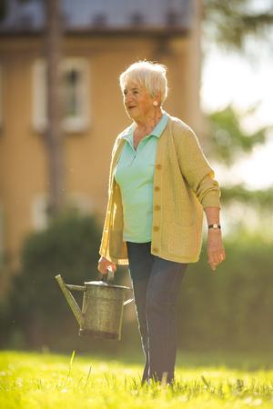 Photo pour Senior woman doing some gardening in her lovely garden - image libre de droit