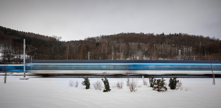 Foto per Trains going fast throught a small town train station - motion blurred image. High speed passenger train in motion. Modern intercity train. Railway transportation - Immagine Royalty Free
