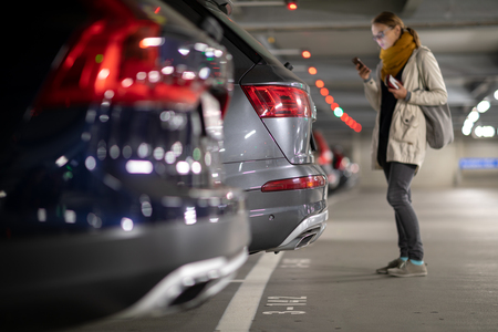 Photo for Underground garage or modern car parking with lots of vehicles, perspective of the row of the cars with a female driver looking for her vehicle - Royalty Free Image