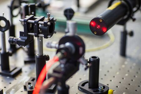 Foto de Quantum optics lab installations with laser, irises, appertures - laser reflect on optic table un quantum laboratory - Imagen libre de derechos