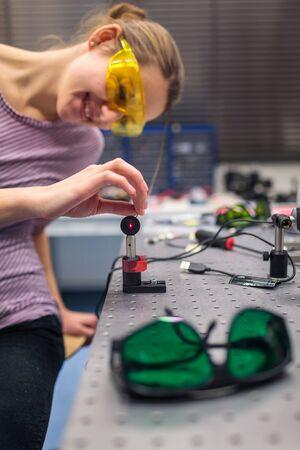 Foto de Female scientist carrying out research experiments in a quantum optics lab (color toned image) - Imagen libre de derechos