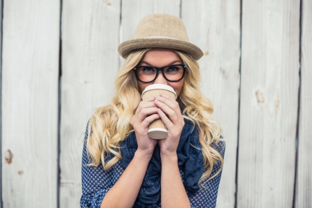 Smiling fashionable blonde drinking coffee outdoors on wooden wall
