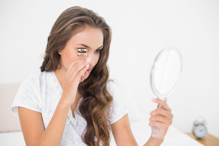 Photo pour Content attractive brunette using an eyelash curler and mirror in bright bedroom - image libre de droit