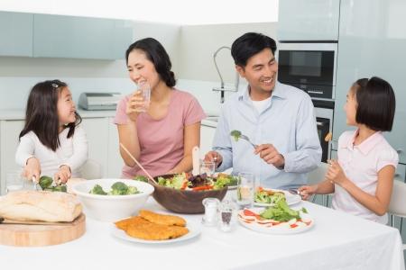 Foto de Young family of four enjoying healthy meal in the kitchen at home - Imagen libre de derechos