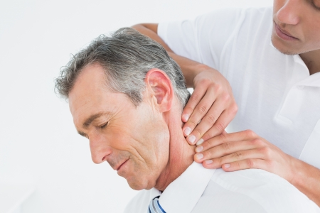 Photo for Close-up of a male chiropractor massaging patients neck over white background - Royalty Free Image