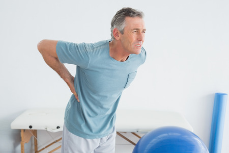 Photo pour Mature man with lower back pain standing in the gym at hospital - image libre de droit