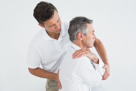 Photo for Side view of a male chiropractor examining mature man over white background - Royalty Free Image