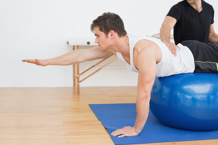 Photo for Physical therapist assisting young man with yoga ball in the gym at hospital - Royalty Free Image