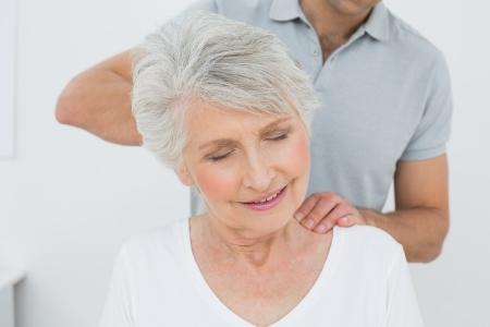 Photo pour Male physiotherapist massaging a senior woman's neck in the medical office - image libre de droit