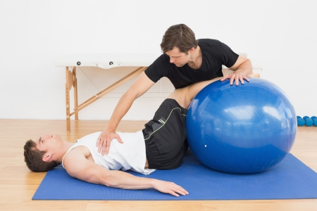 Foto de Physical therapist assisting young man with yoga ball in the gym at hospital - Imagen libre de derechos