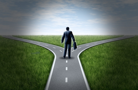 Business man at a cross roads standing at a horizon with grass and blue sky showing a fork in the road representing the concept of a strategic dilemma choosing the right direction to go when facing two equal or similar options.