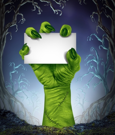 Zombie rising hand holding a blank sign card as a spooky halloween or scary symbol with textured green skin and monster fingers with stitches in a foggy night time tree forest background as a cemetary like creepy place