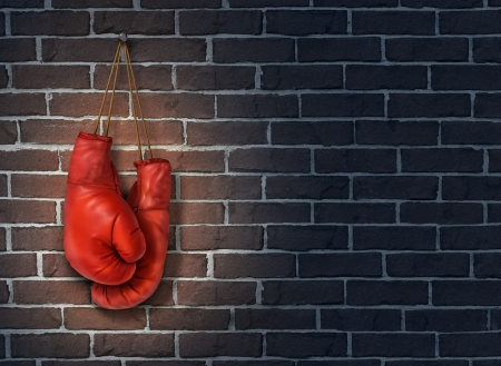 Stop competing and putting an end to business competition by hanging up a pair of red boxing gloves on a dark rustic old brick wall as a concept of stopping the fight to find the cure