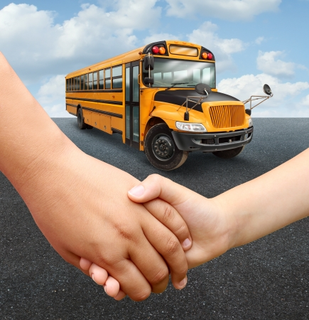 Foto de School children bus with two young students of elementary age holding hands preparing to go into the yellow transport vehicle as an education and learning concept  - Imagen libre de derechos