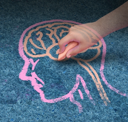 Foto de Children education concept  and school learning development with the hand of a child drawing a human head and brain with chalk on a cement floor as a symbol of mental health issues in youth  - Imagen libre de derechos