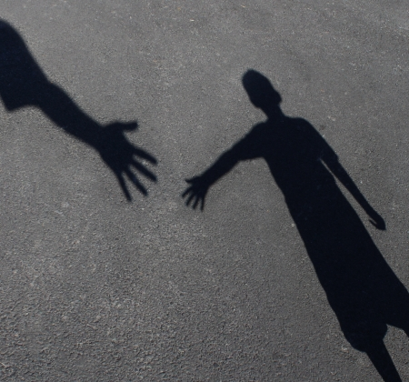 Foto de Helping Hand with a shadow on pavement of an adult hand offering help or therapy to a child in need as an education concept of charity towards needy kids and teacher guidance to students who need tutoring  - Imagen libre de derechos